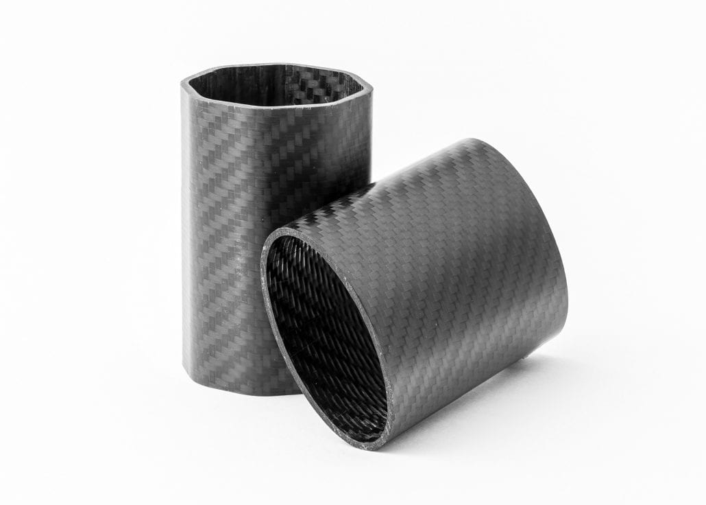 hexagonal carbon fibre tube next to a round carbon fibre tube on its side